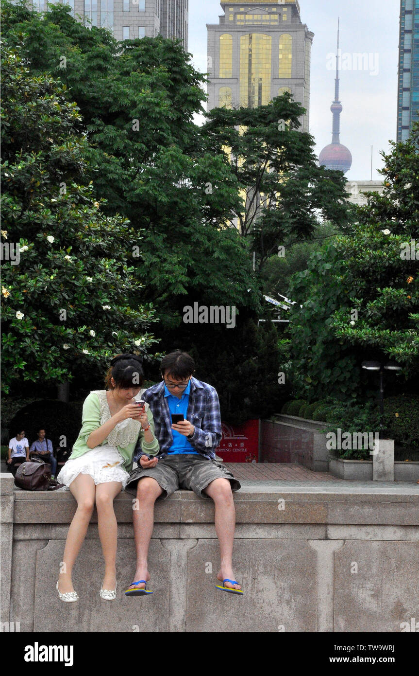 Chinese couple absorbed in their cell phones - Stock Image