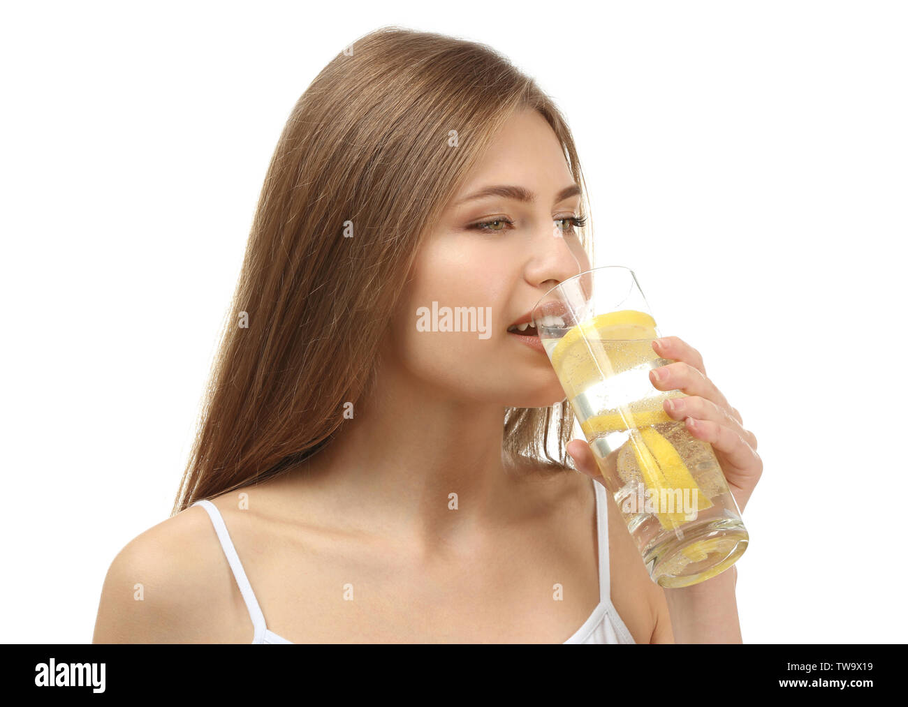 Beautiful young woman drinking fresh lemonade on white background - Stock Image