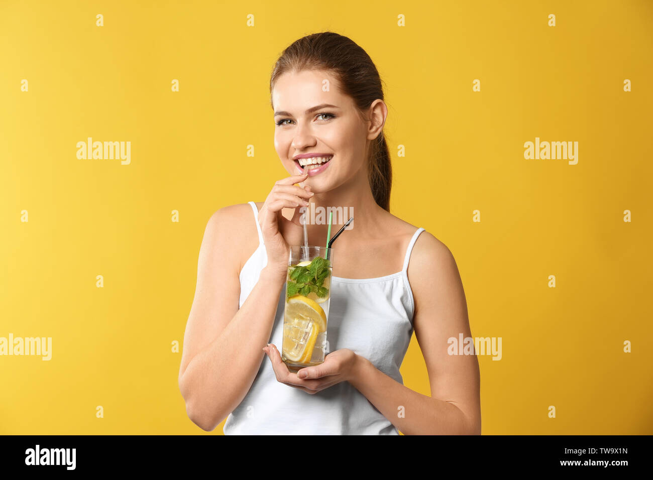 Beautiful young woman drinking lemonade on color background - Stock Image