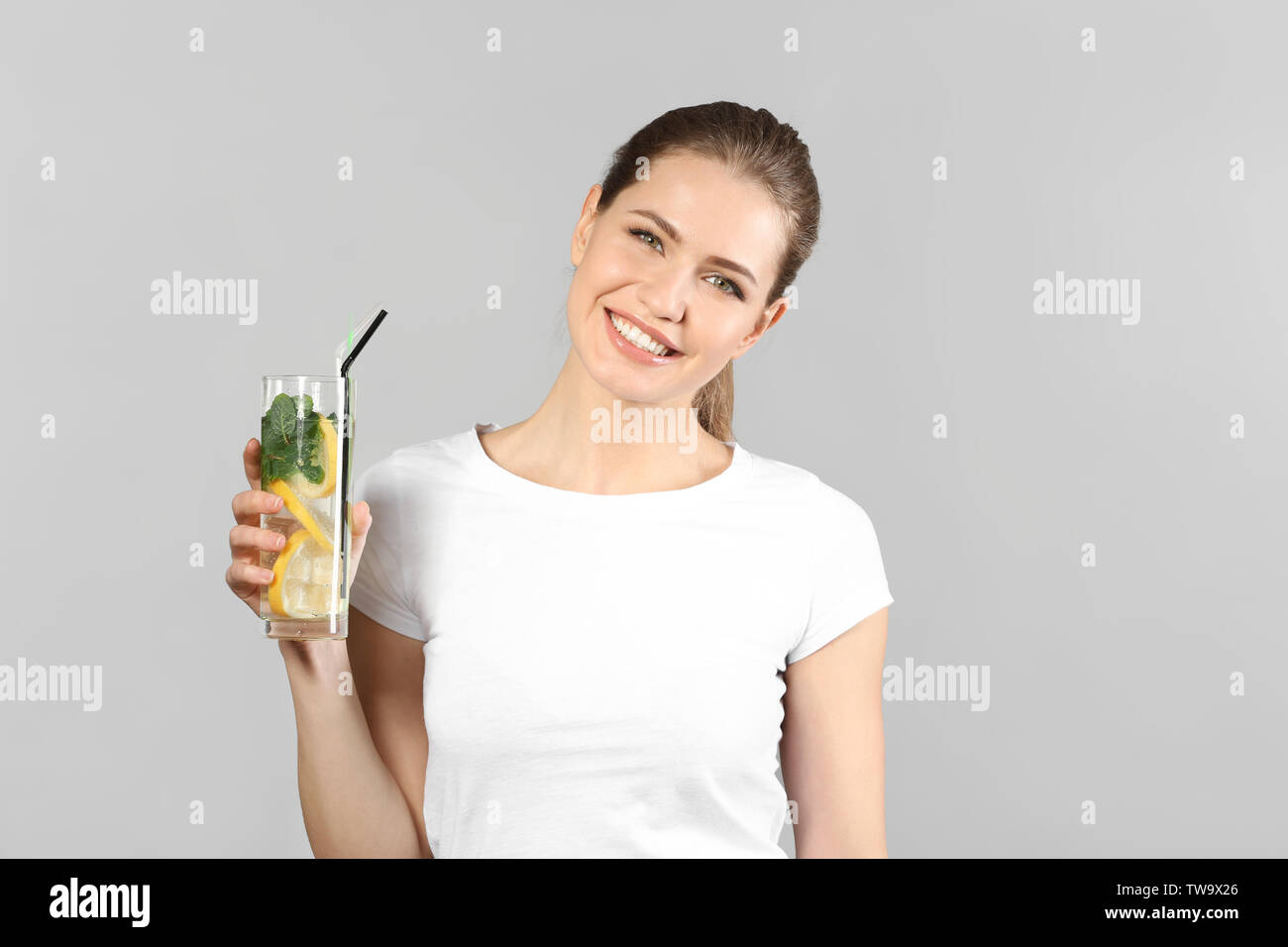 Beautiful young woman with glass of lemonade on grey background - Stock Image