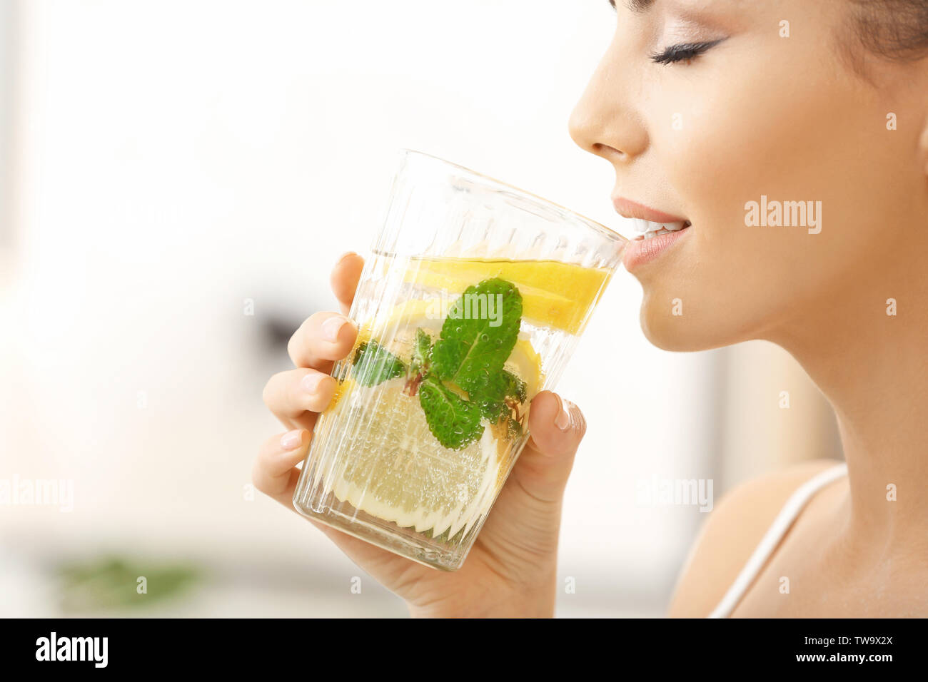 Beautiful young woman drinking fresh lemonade at home, closeup - Stock Image