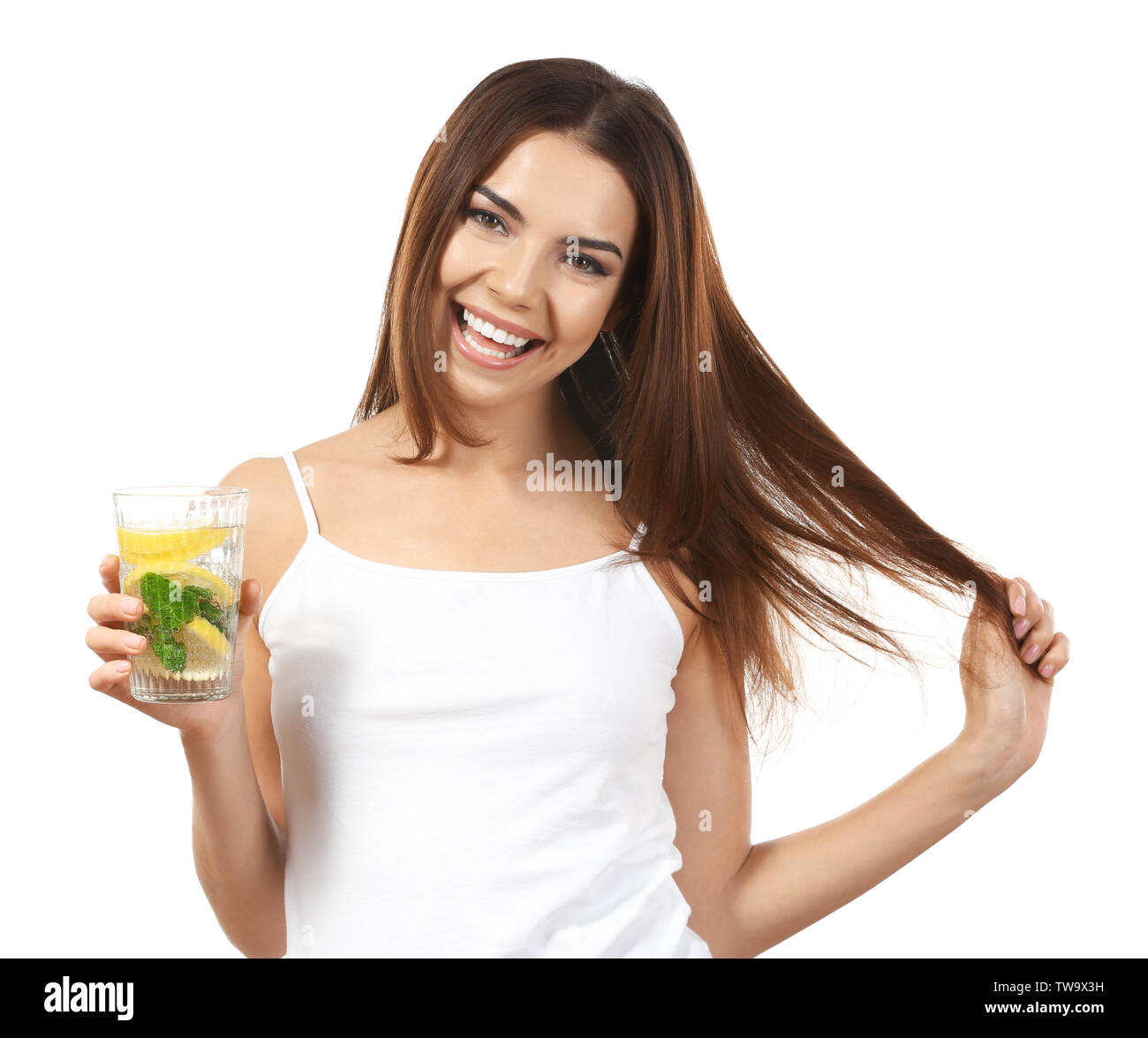 Beautiful young woman with glass of lemonade on white background - Stock Image
