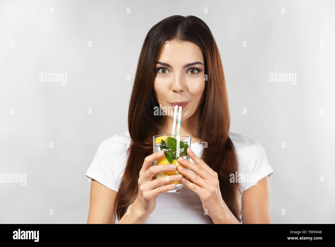 Beautiful young woman drinking lemonade on grey background - Stock Image