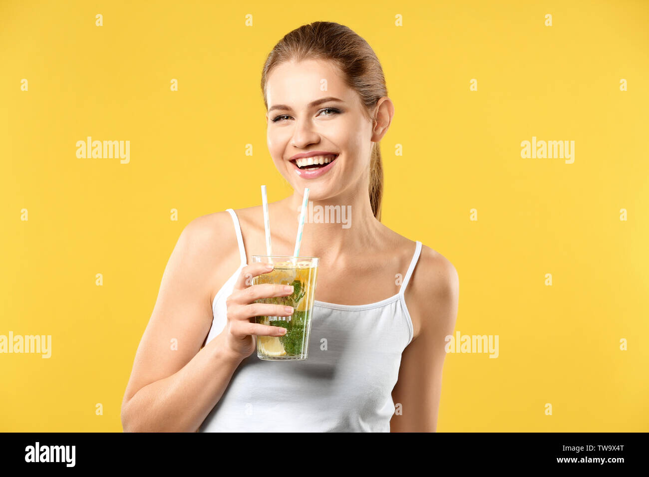 Beautiful young woman with glass of lemonade on color background - Stock Image