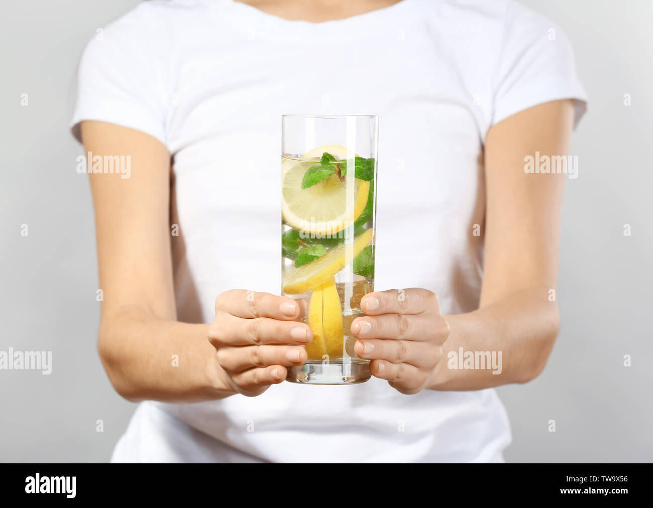Young woman with glass of lemonade on grey background, closeup - Stock Image