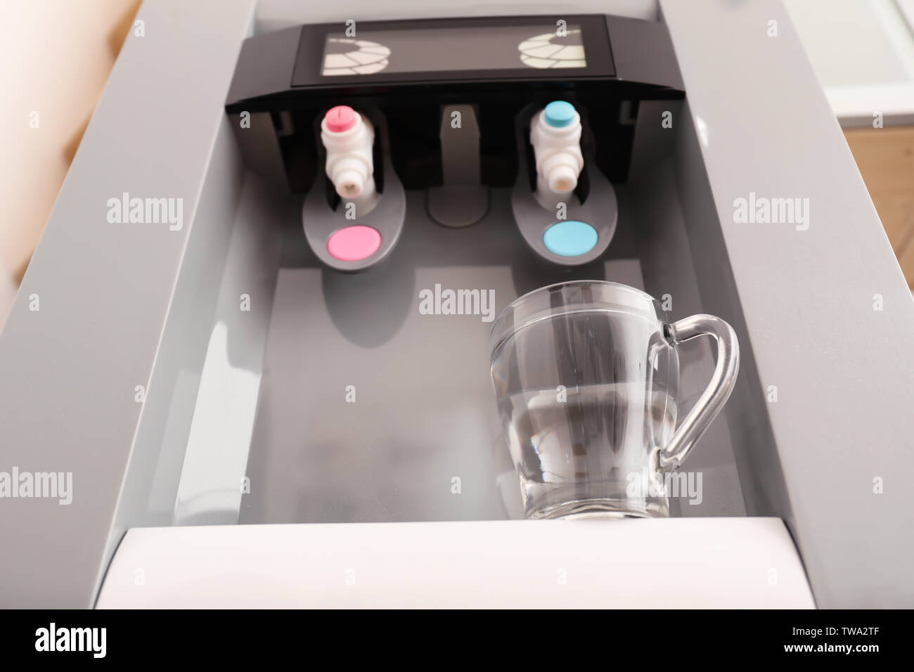 Office water cooler with glass cup, closeup - Stock Image