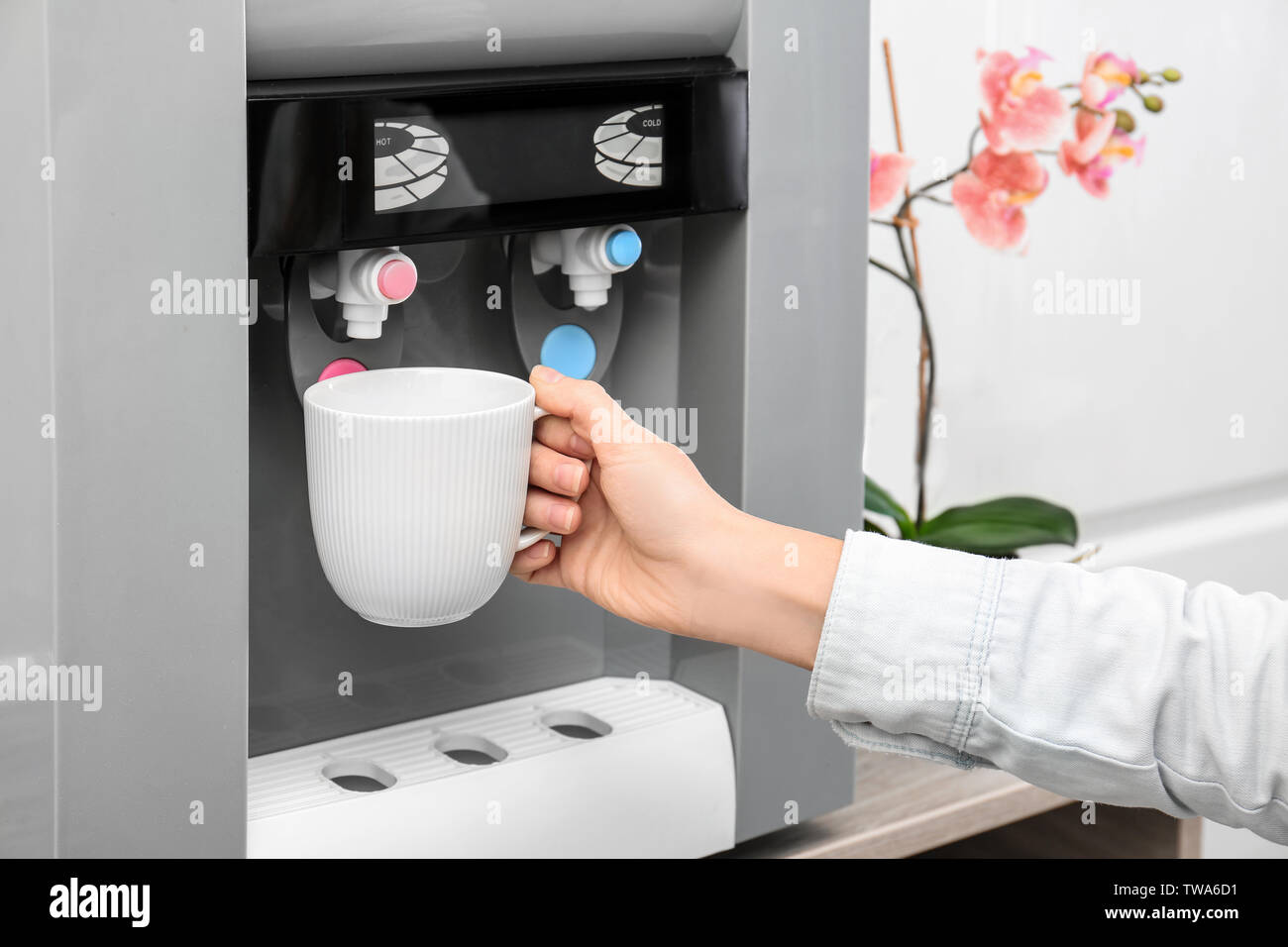 Woman filling cup from water cooler, closeup - Stock Image