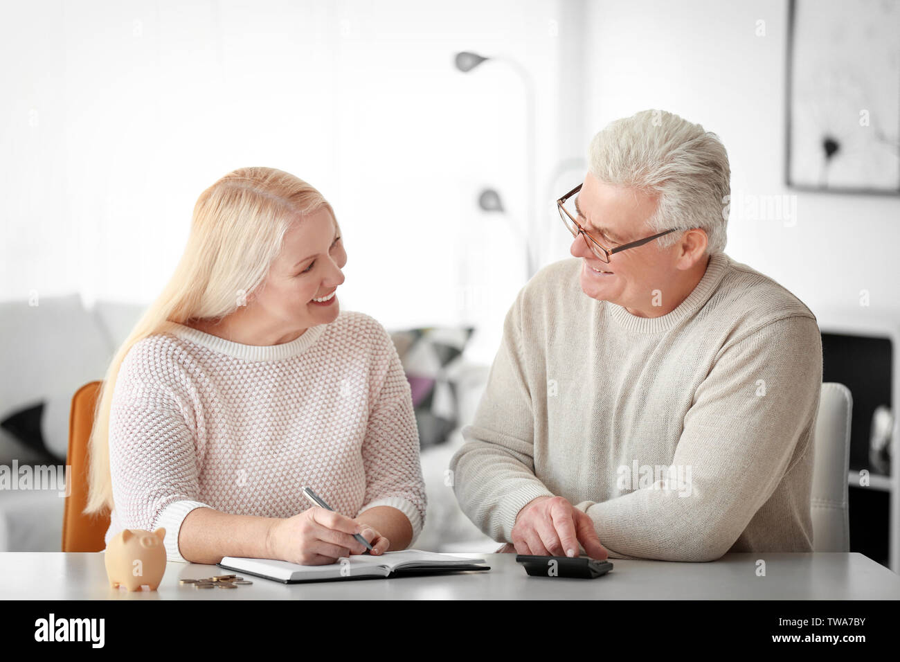 Mature couple thinking over pension plan at home - Stock Image