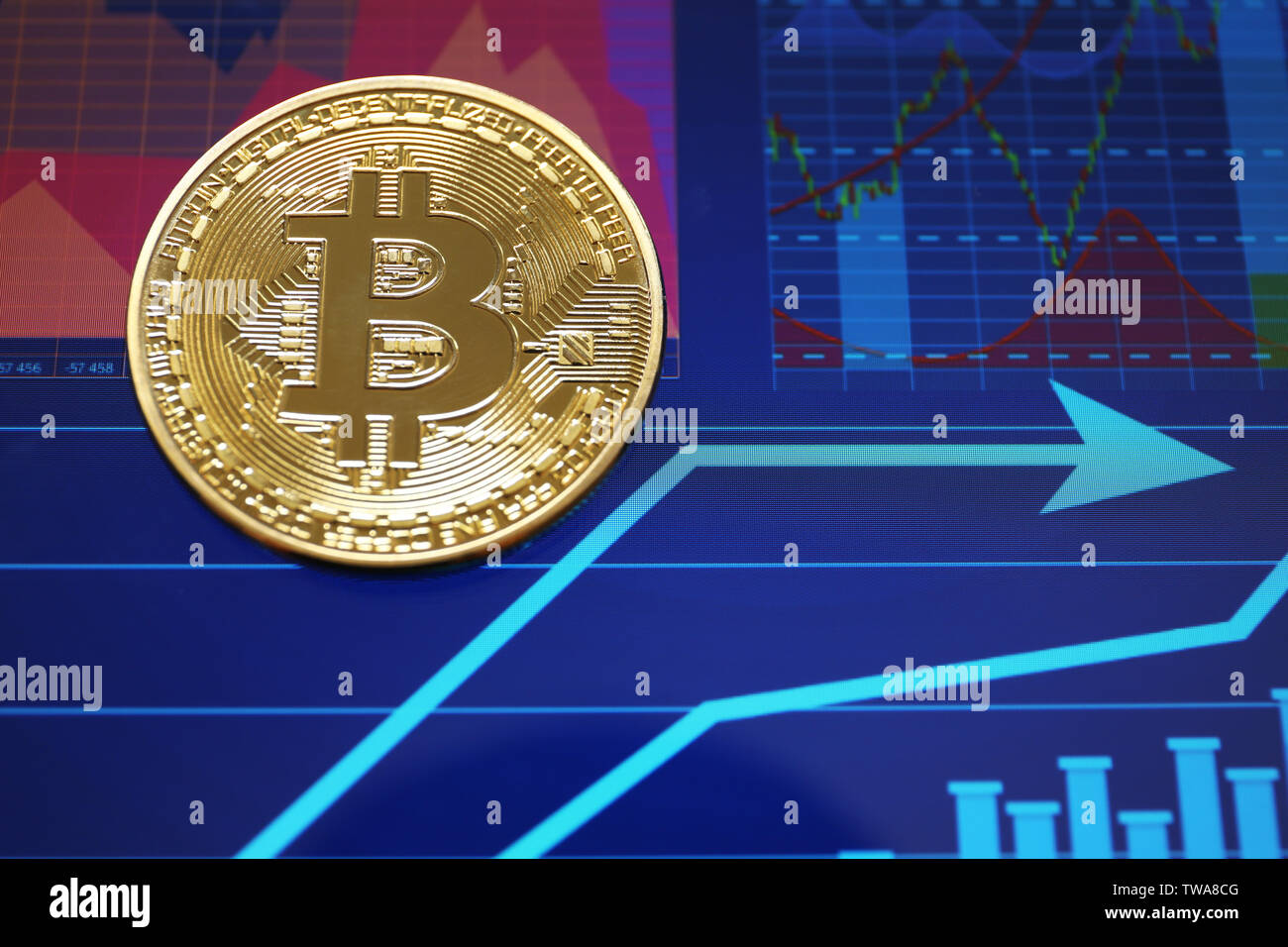 Golden bitcoin on screen with chart. Finance trading - Stock Image