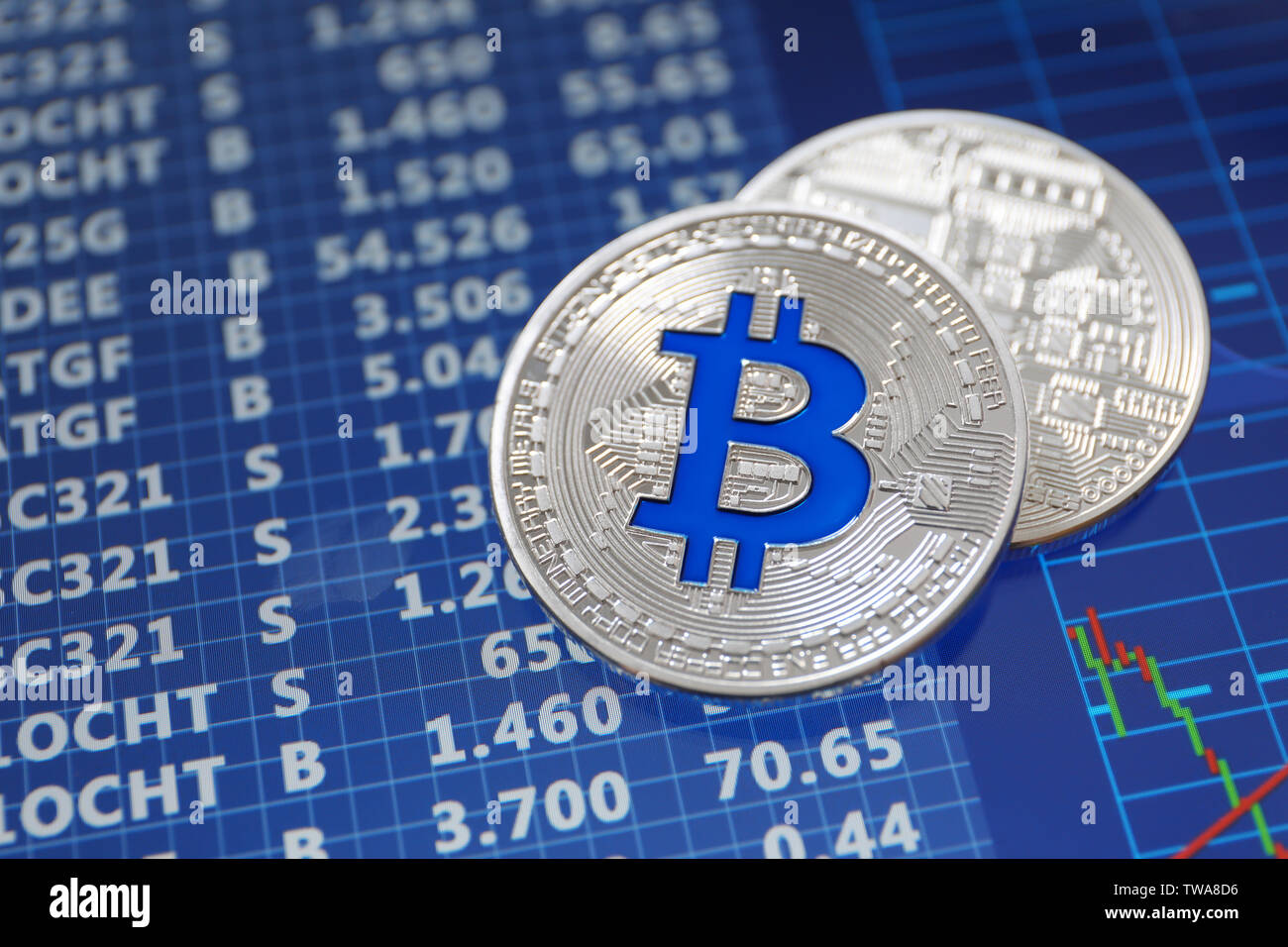 Silver bitcoins on screen with exchange rates. Finance trading - Stock Image