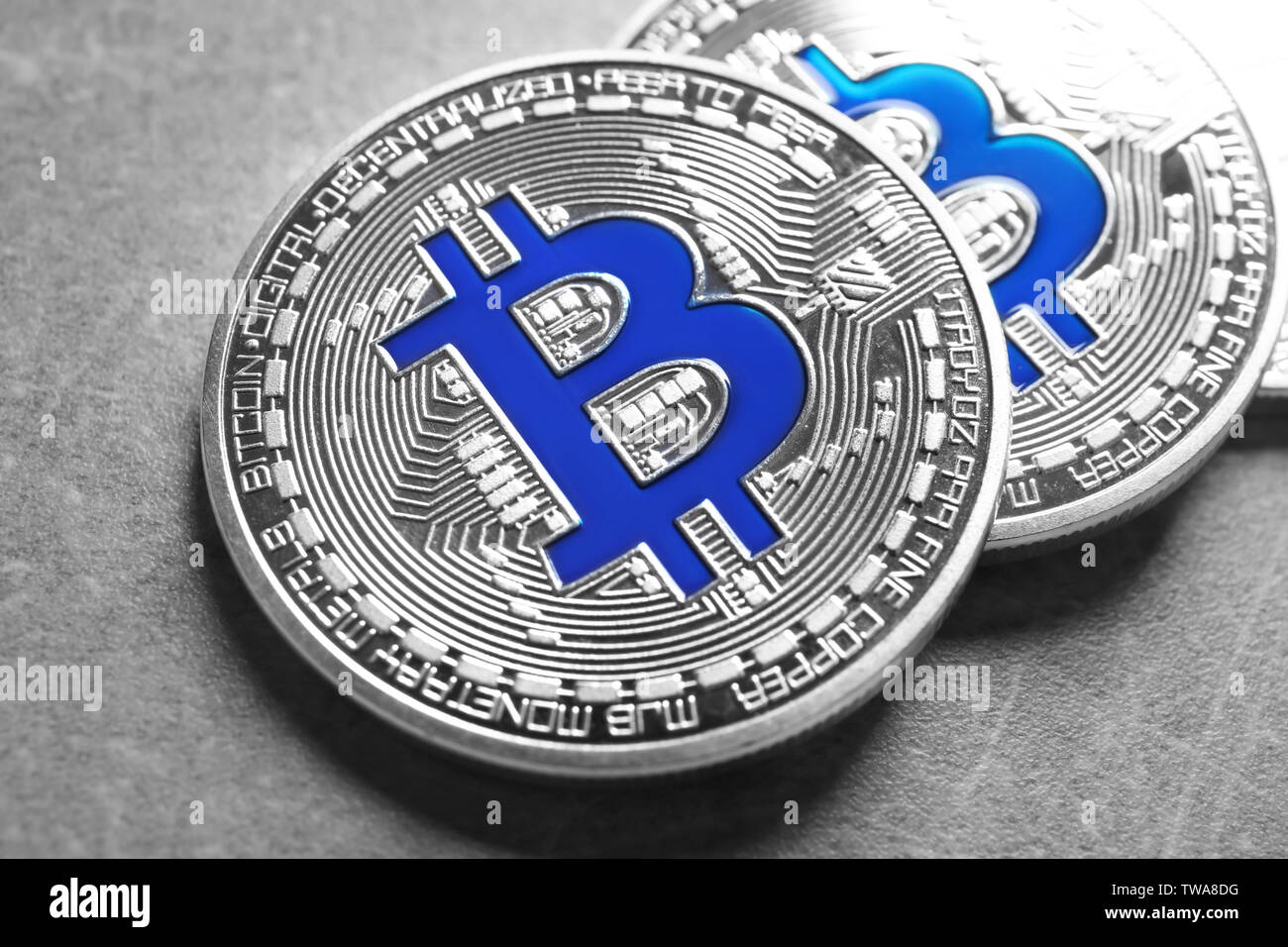 Silver bitcoins on grey background. Finance trading - Stock Image