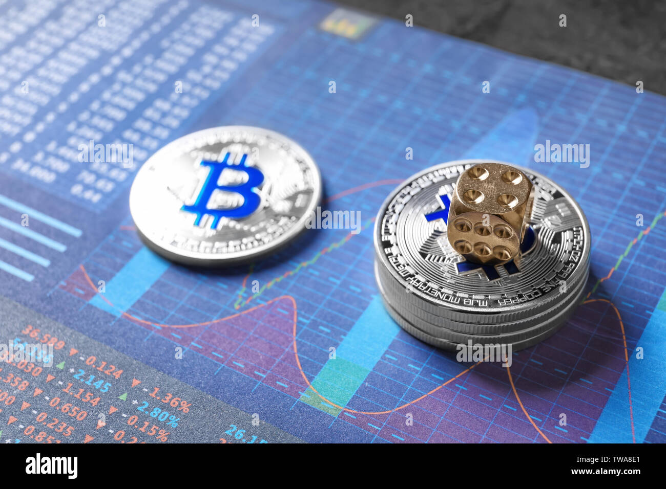 Silver bitcoins and dice on chart. Finance trading - Stock Image