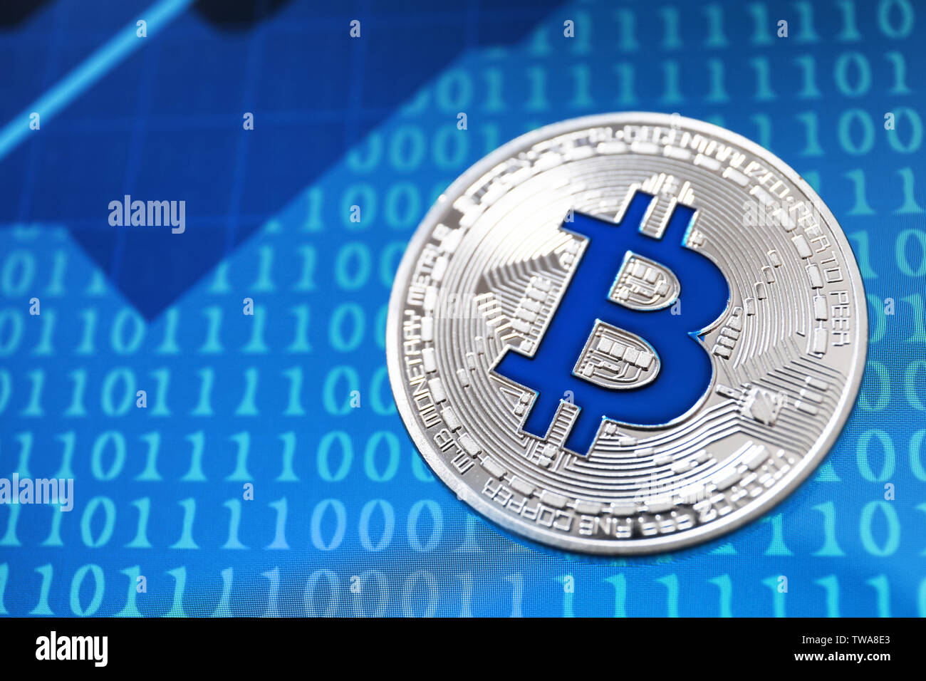 Silver bitcoin on screen with numbers. Finance trading - Stock Image