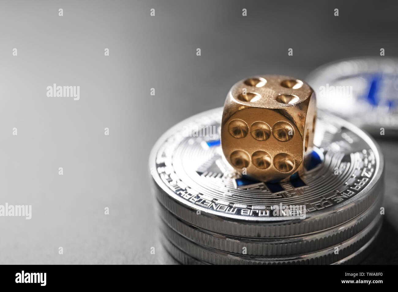Silver bitcoins and dice on grey background. Finance trading - Stock Image