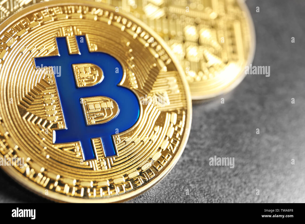 Golden bitcoins on grey background. Finance trading - Stock Image