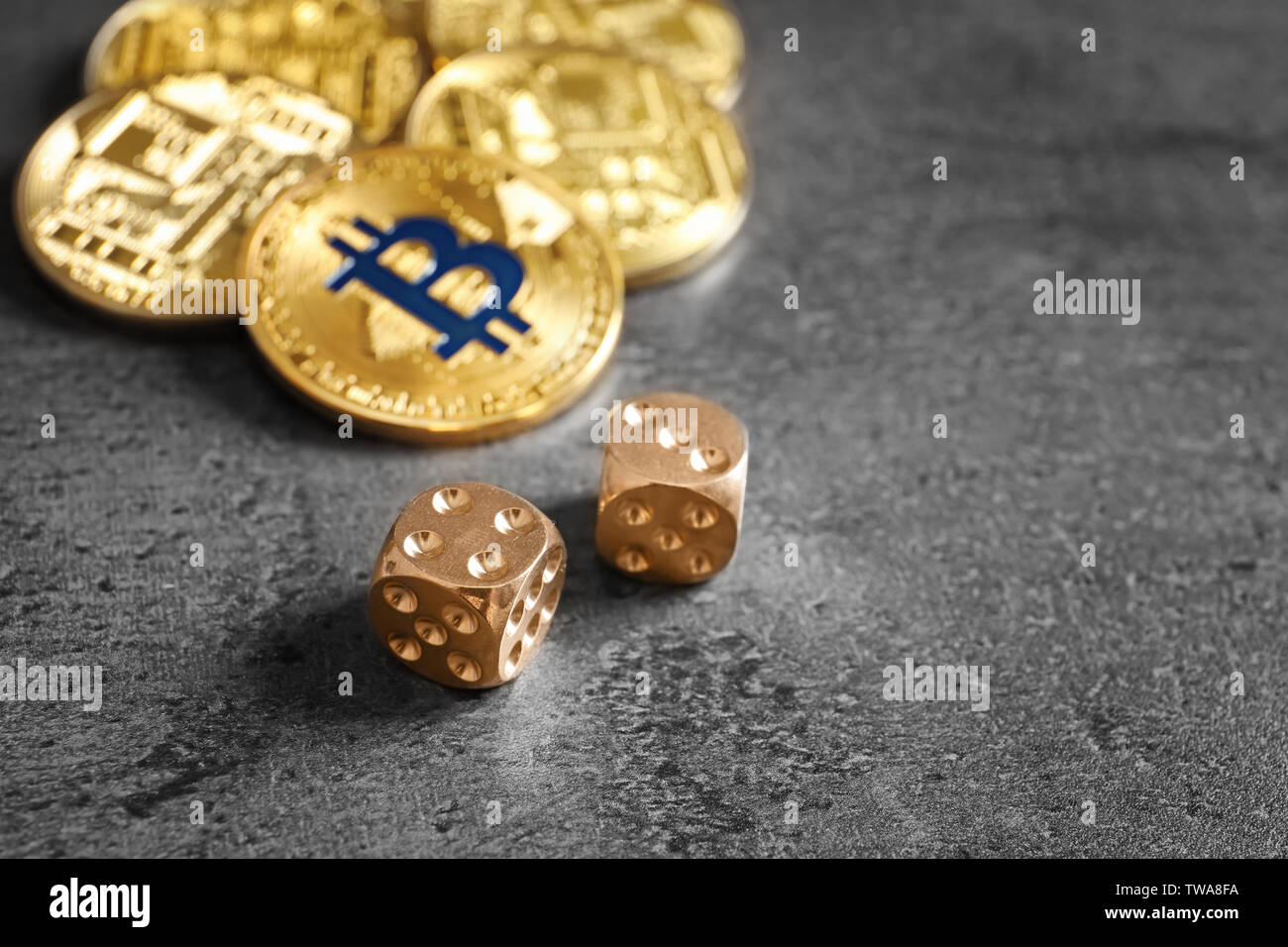 Golden bitcoins and dice on grey background. Finance trading - Stock Image