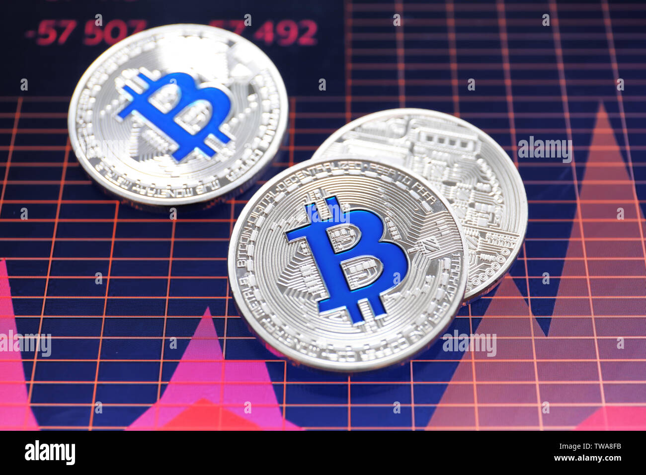 Silver bitcoins on screen with chart. Finance trading - Stock Image