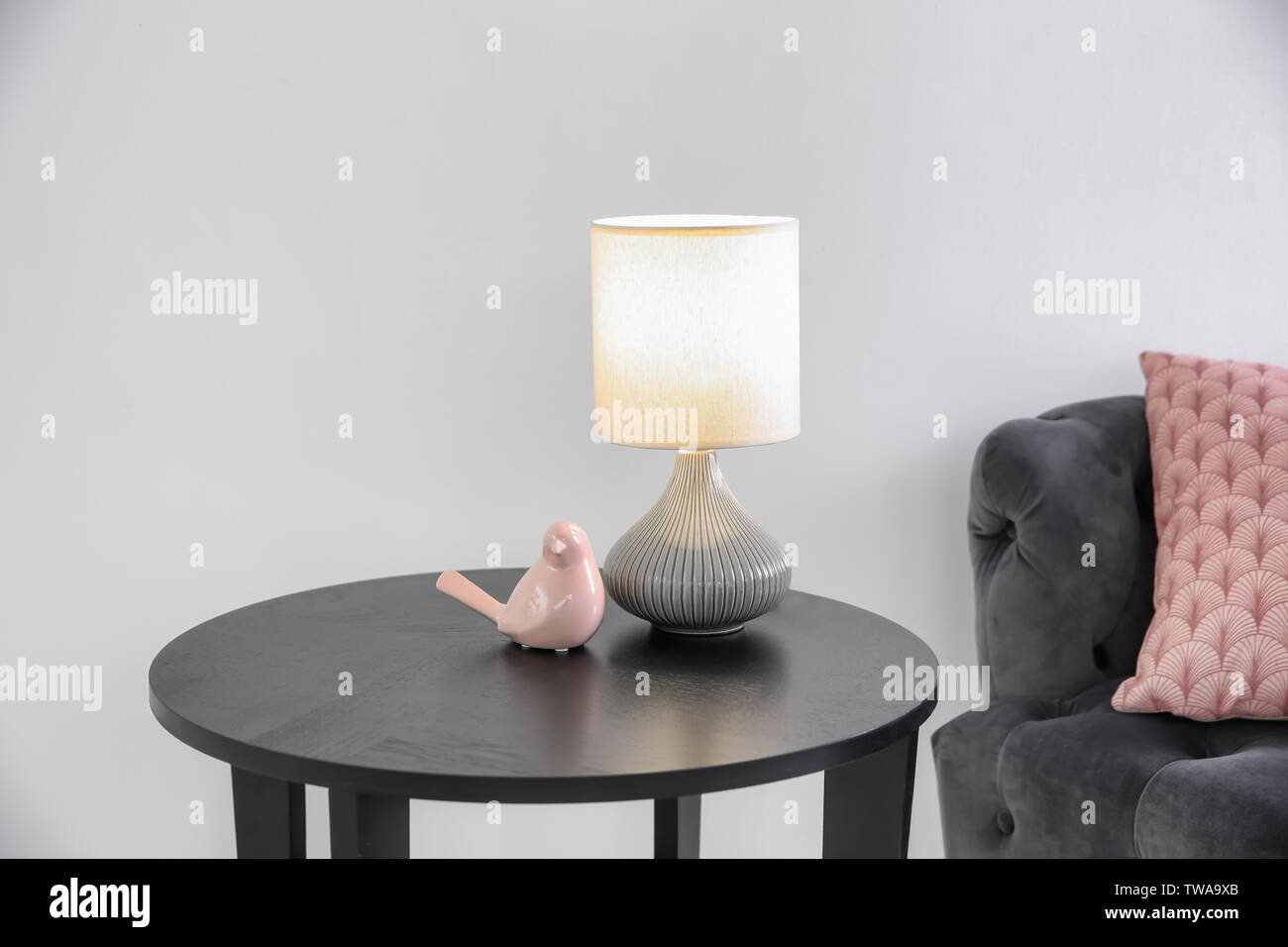 Side Table With Stylish Lamp Near White Wall Stock Photo