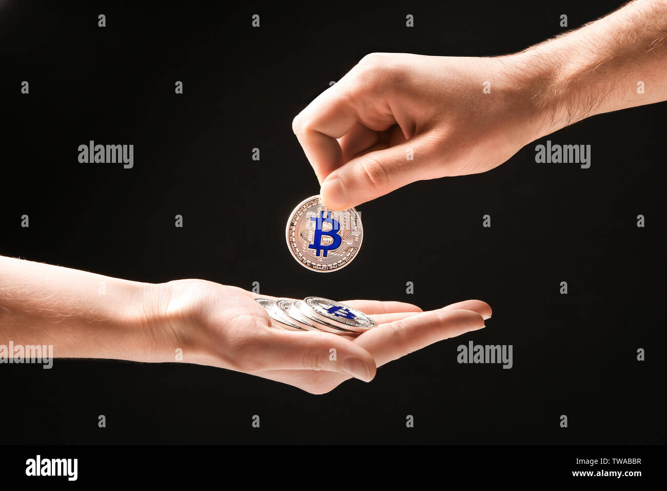 Man giving silver bitcoin to woman on black background - Stock Image