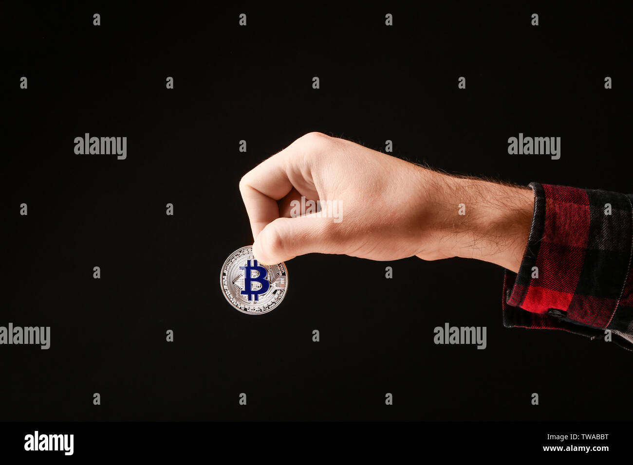 Man holding silver bitcoin on black background - Stock Image