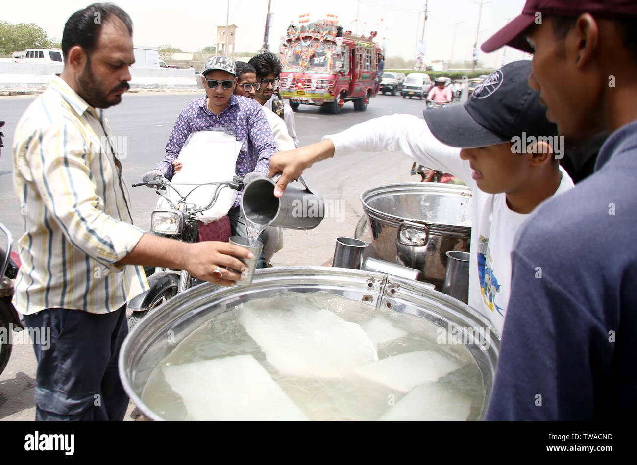 Citizens are quenching their thirst by chilled water to beat the heat of sun during the hot day of summer season, at a relief camp of heat stroke organized by Social Organization, located on Shahrah-e-Faisal road in Karachi on Tuesday, June 18, 2019. - Stock Image