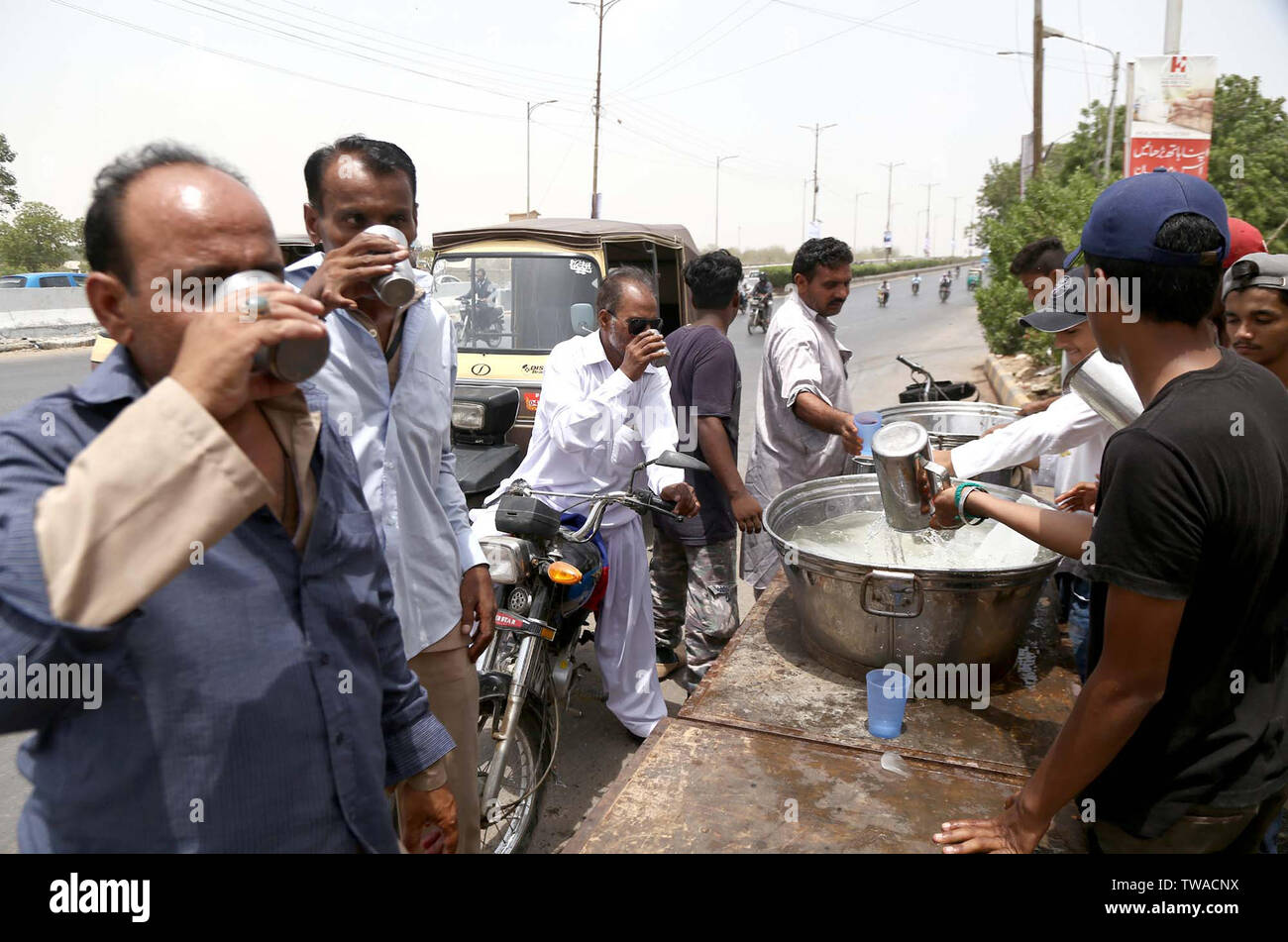 Citizens are quenching their thirst by chilled water to beat the heat of sun during the hot day of summer season, at a relief camp of heat stroke organized by Social Organization, located on Shahrah-e-Faisal road in Karachi on Tuesday, June 18, 2019 - Stock Image