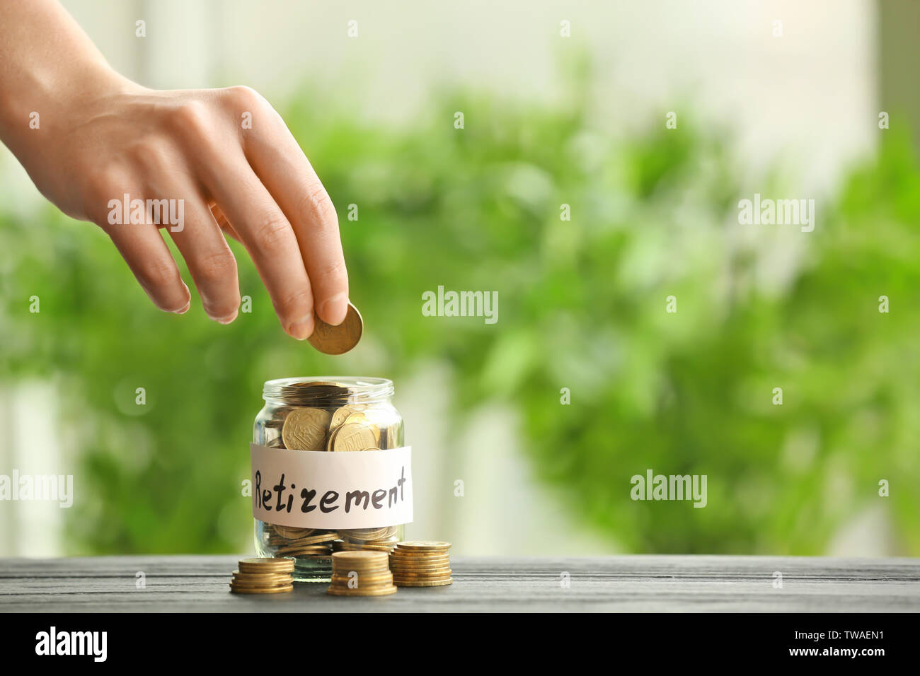 Hand putting coin into glass jar against blurred background. Pension planning concept - Stock Image
