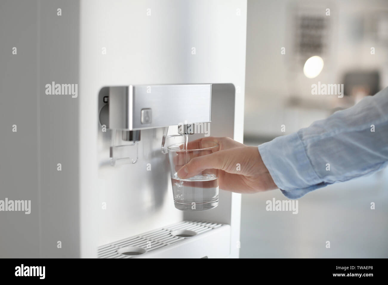 Woman filling glass from water cooler, closeup - Stock Image