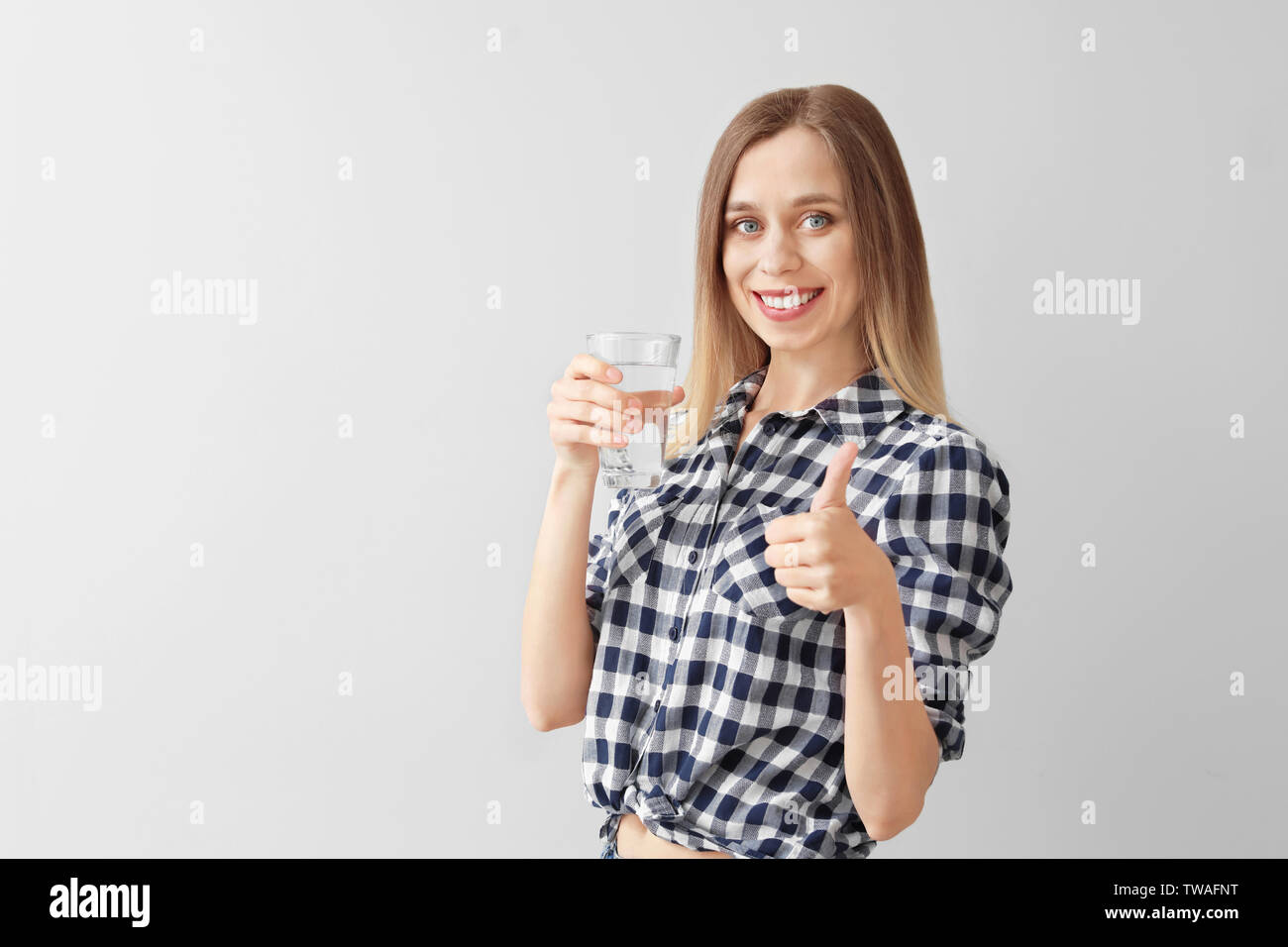 Beautiful young woman with glass of water showing thumb-up gesture on light background - Stock Image