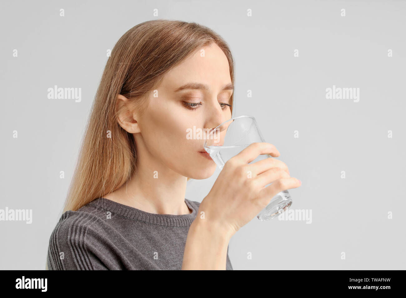 Beautiful young woman drinking water on light background - Stock Image