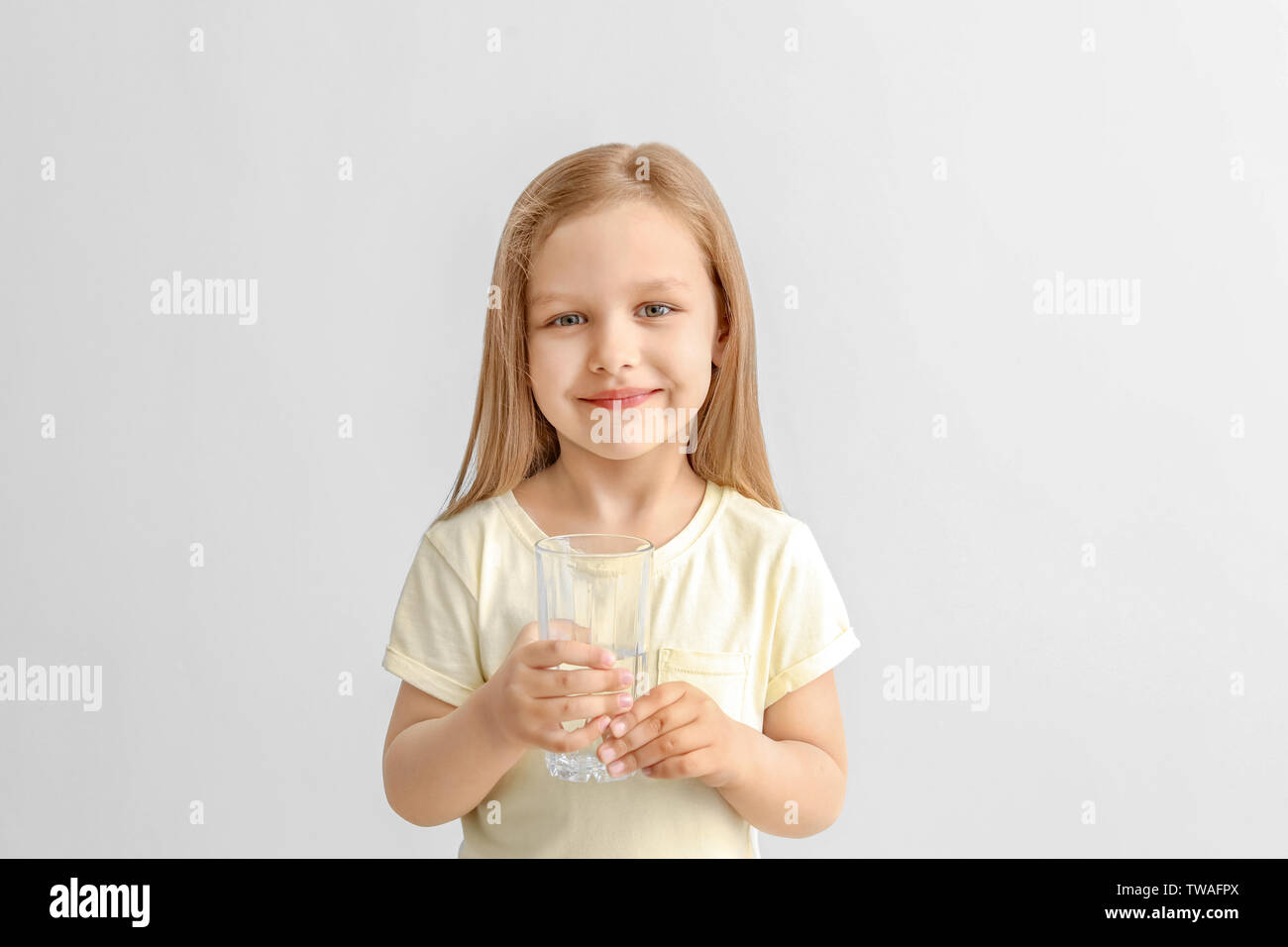 Cute little girl with glass of water on light background - Stock Image