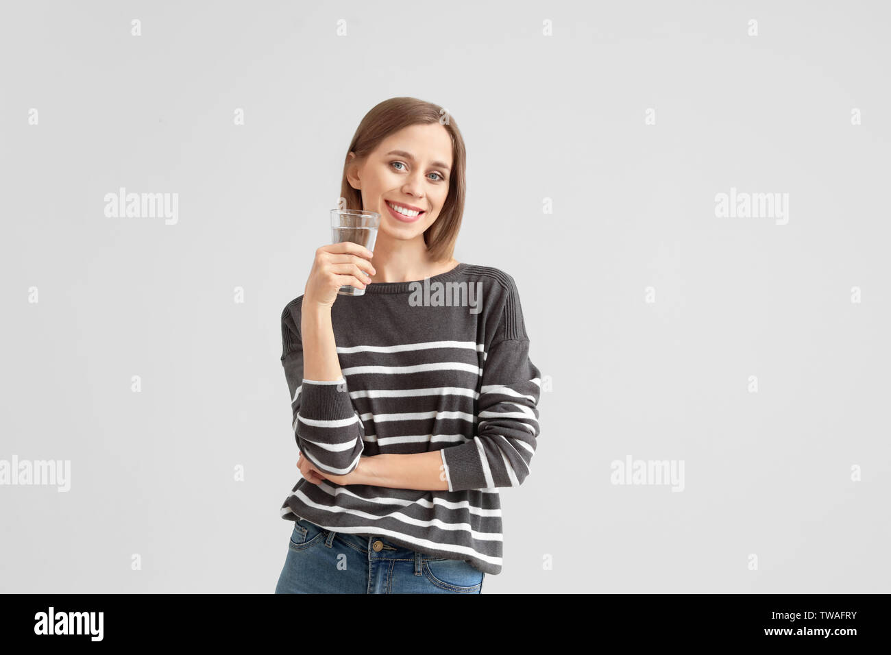 Beautiful young woman with glass of water on light background - Stock Image
