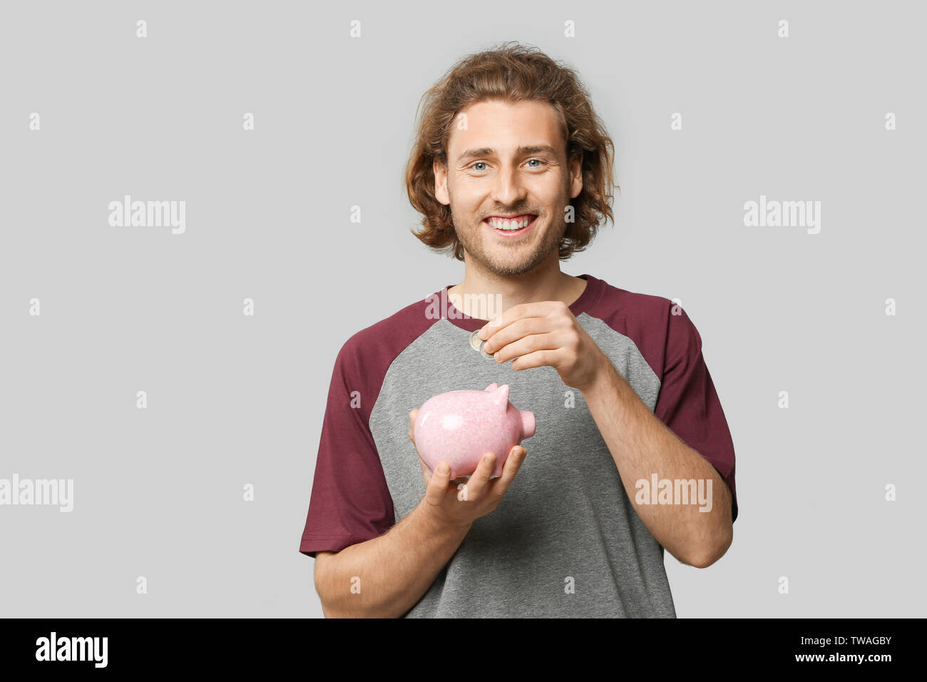 Handsome man with piggy bank on grey background - Stock Image