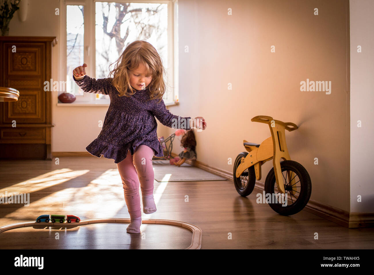 Happy, little child girl playing and dancing inside toy train tracks, in a sunlit room with window, having fun during her playtime Stock Photo