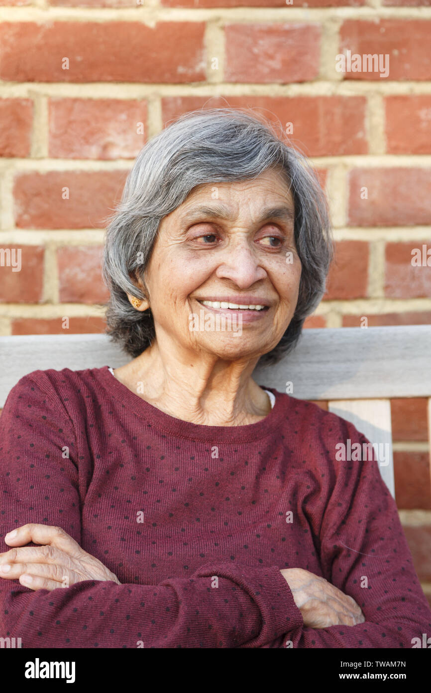 547e220549 Old elderly Asian Indian woman sitting with a smiling face, depicting  health and happiness in