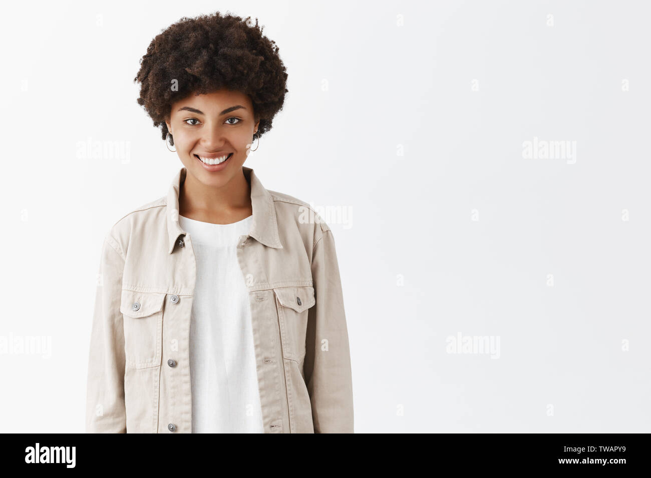Indoor Shot Of Cute Tomboy Girl With Dark Skin And Afro Hairstyle In