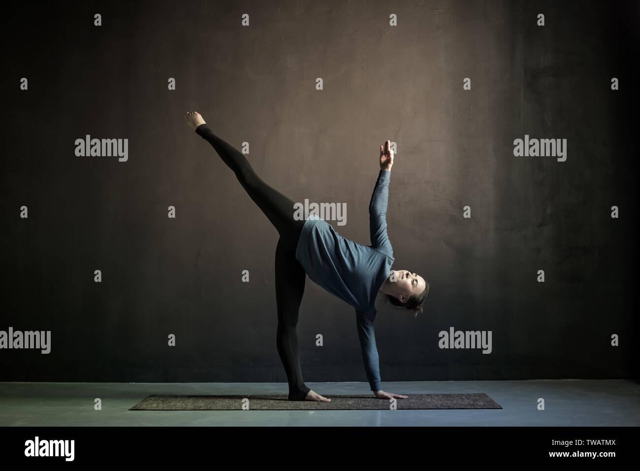 woman practicing yoga in Half Moon exercise, Ardha Chandrasana pose - Stock Image