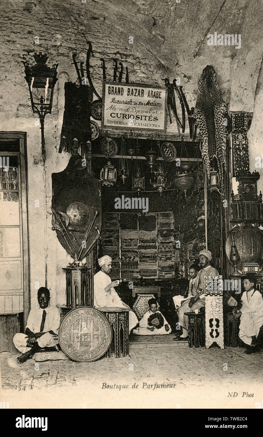 Grand Arabian Bazar, Tunis, Tunisia - Perfume Shop (Boutique de Parfumier), also selling numerous and multiple Tourist items, curiosities and knick knacks, including traditional fabric, metalwork and weaponry!     Date: circa 1910 - Stock Image