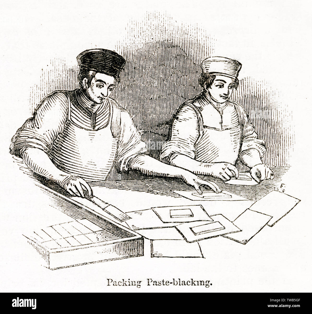 Scene inside the Day and Martin blacking factory, Holborn, London -- two men pack soft paste blacking in rectangular form in oiled paper wrappers.      Date: 1842 - Stock Image