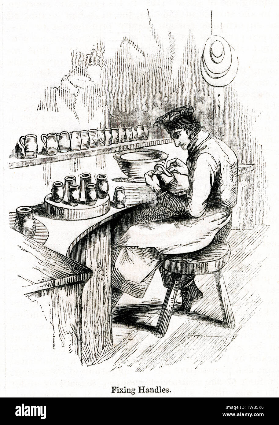 Scene at the Royal Porcelain Works, Worcester -- man sitting at a bench, fixing handles onto jugs.      Date: 1843 - Stock Image