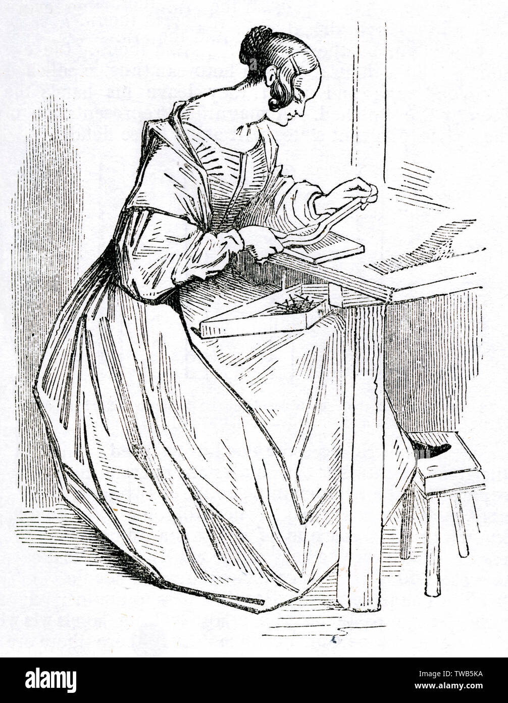 Scene at the British Needle Mills, Redditch, Worcestershire -- woman doing separating and straightening work with a steel bar towards the end of the manufacturing process, and dropping the finished product into a tray on her lap.      Date: 1843 - Stock Image