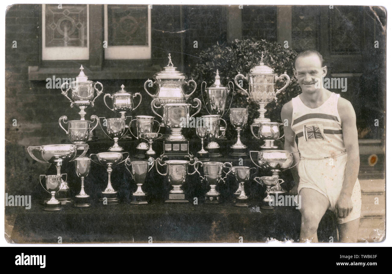 Tommy Green (1894-1975), British racewalker and 50,000 metres gold medallist in the 1932 Summer Olympics (held in Los Angeles, USA), photographed with 24 trophies.      Date: circa 1932 - Stock Image
