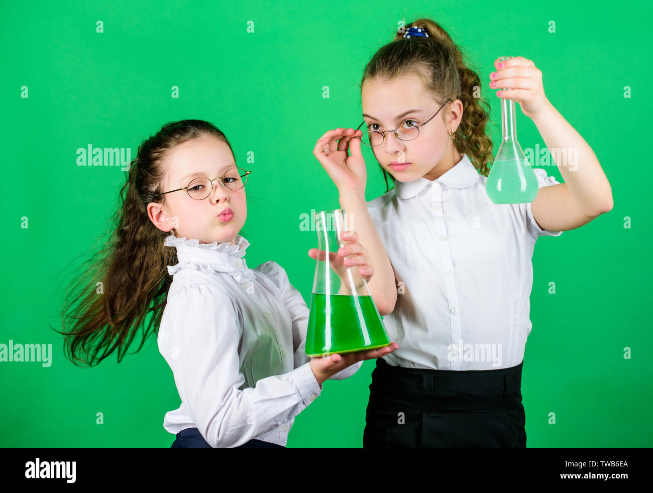 The formula is almost complete. school kid scientist studying science. children study chemistry lab. little smart girls with testing flask. biology education. back to school. formula concept. formula. - Stock Image
