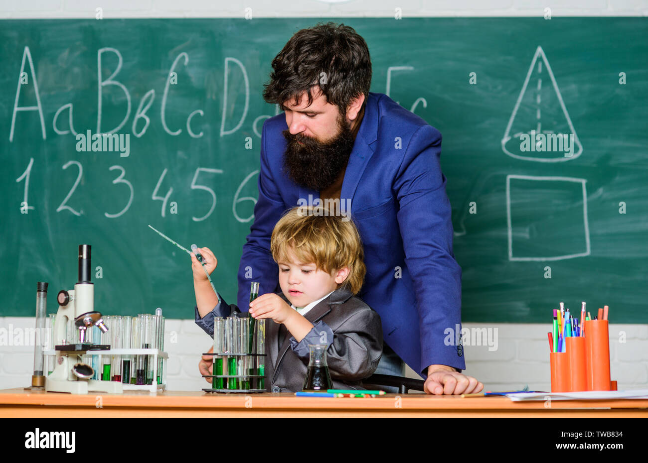 bearded man teacher with little boy. father and son at school. Pupil kid in the chemistry class confidence charisma. Back to school. Science chemistry concept. Focused on exam. - Stock Image