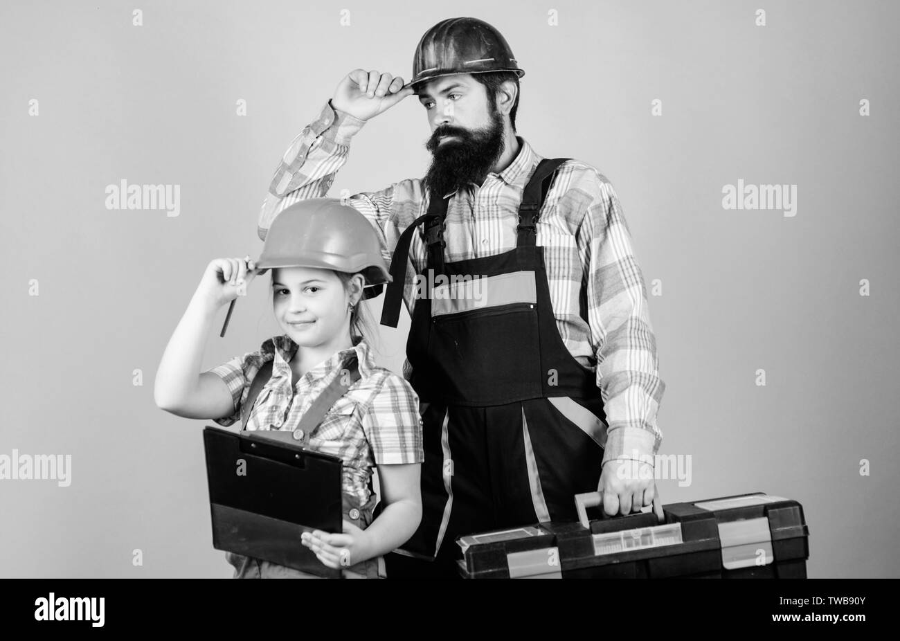 Father and daughter in workshop. Bearded man with little girl. construction worker assistant. Builder or carpenter. Repairman in uniform. Engineer. Repair. Childrens creativity. team at work. - Stock Image