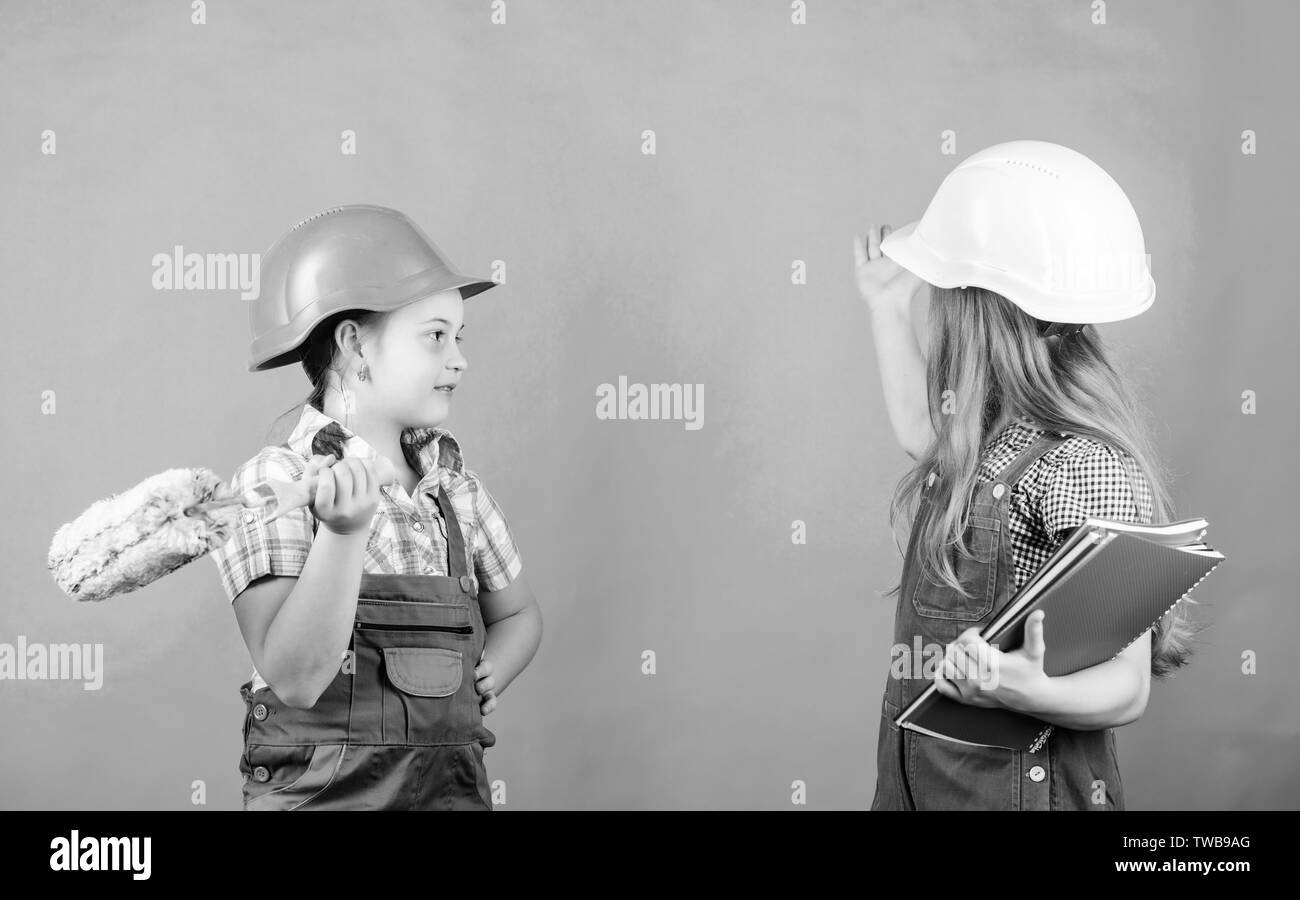 Little kids in helmet with tablet and roller. Labor day. 1 may. school project. Foreman. Repair working process. small girls repairing together in workshop. working process. working process in action. - Stock Image