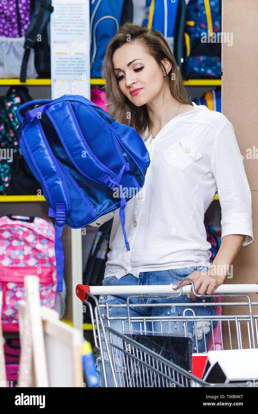 Mother buying school bag in mall. A young woman with a troley is shopping at a supermarket. Stock Photo