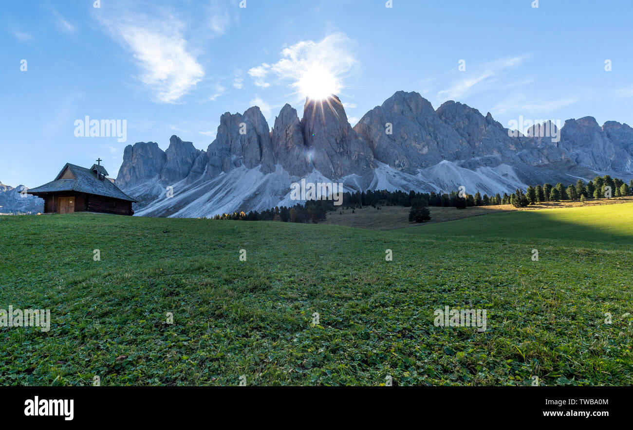 Sunburst over the Odle peaks and chapel at Glatschalm, Puez Odle, Dolomites, Funes, Bolzano province, South Tyrol, Italy Stock Photo