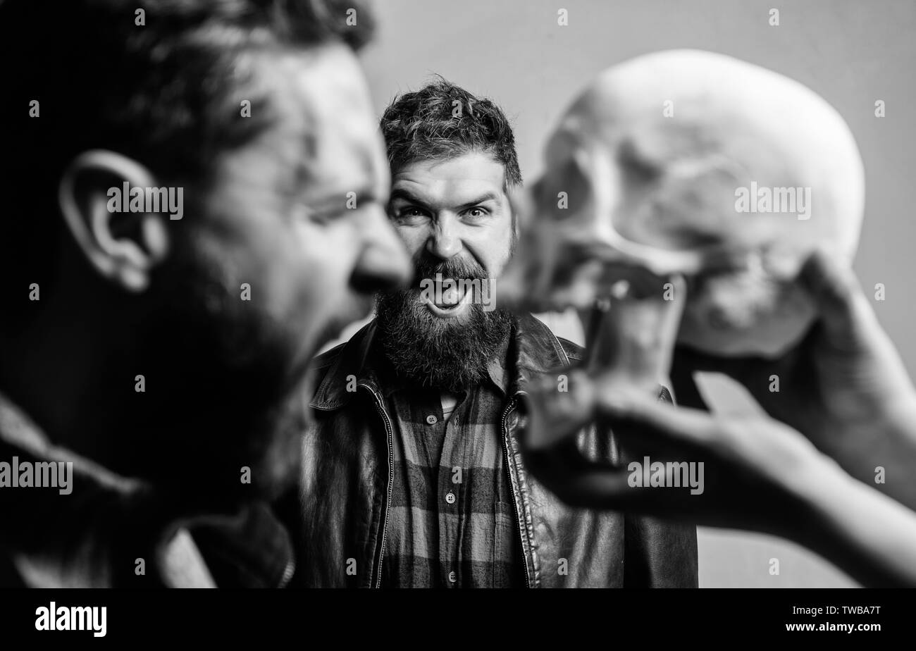 Human fears and courage. Looking deep into eyes of your fear. Man brutal bearded hipster looking at skull symbol of death. Overcome your fears. Be brave. Focused on breaking fear. Psychology concept. - Stock Image