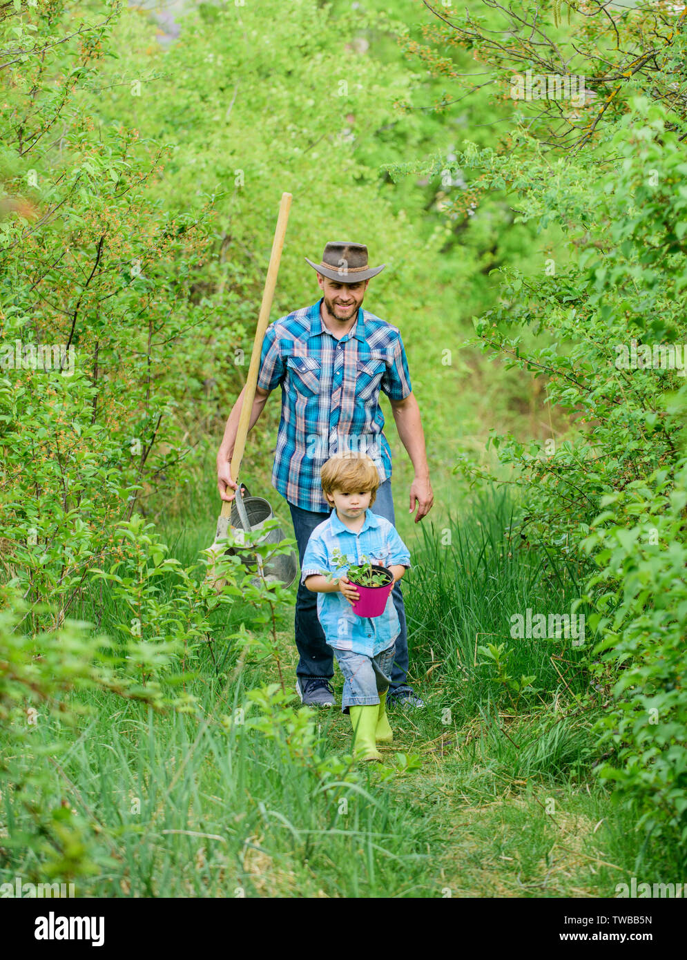 Little helper in garden. Planting flowers. Growing plants. Boy and father in nature with watering can and shovel. Dad teaching son care plants. Arbor day. Planting trees. Tree planting tradition. Stock Photo